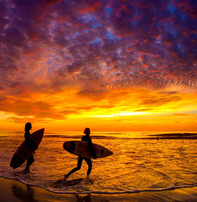 2 surfers against a sunset sky  | North Coastal San Diego CA