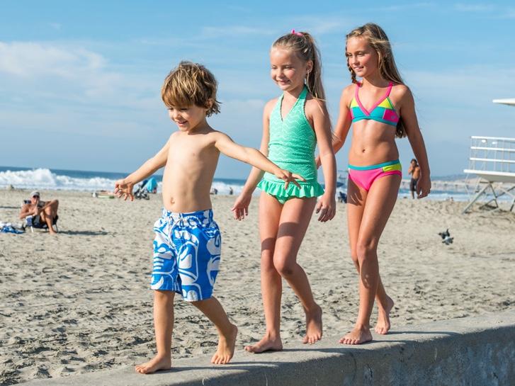 Three kids walking along the seawall at La Jolla Shores
