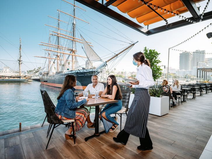 Family dining outdoors at the Portside Pier