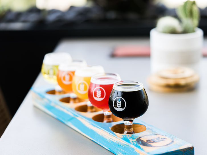 a flight of beers ranging from dark to light on a table