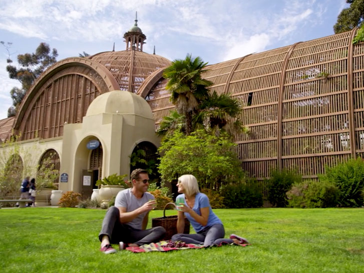 couple sitting on the grass having a picnic in front of the botanic building in balboa park
