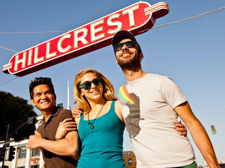 Friends walking un the Hillcrest neighborhood sign
