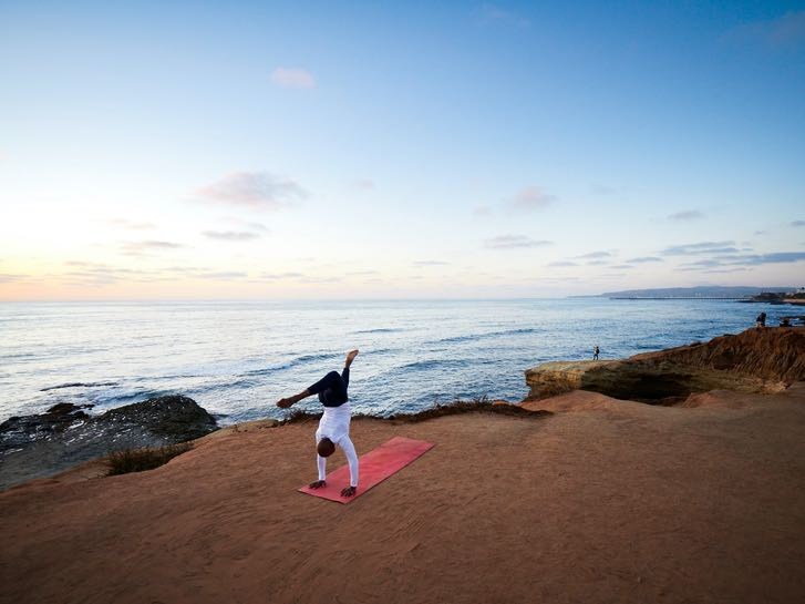 Man getting in a yoga workout at Sunset Cliffs