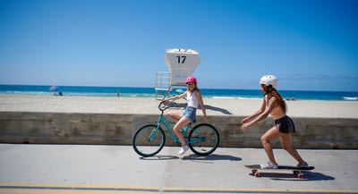 Young ladies riding a bicycle and skateboard along the Mission Beach Boardwalk in San Diego