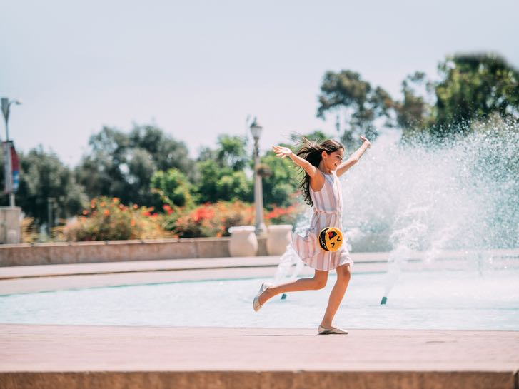 Young girl playing at the Bae Evenson Fountain in Balboa Park for Kids Free San Diego