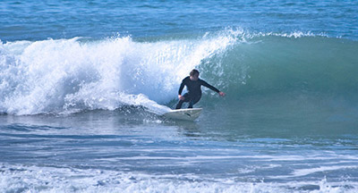 Surfer catching a wave in Carlsbad