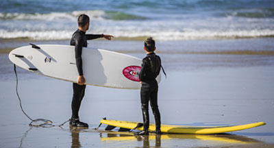 Dad and kid surfers at La Jolla Shores in San Diego CA