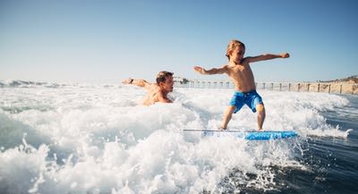 Dad and Son playing in the ocean - Water Activities and Things to Do in San Diego, California