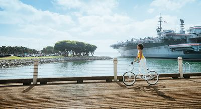 Woman riding a bicycle along the Embarcadero in San Diego